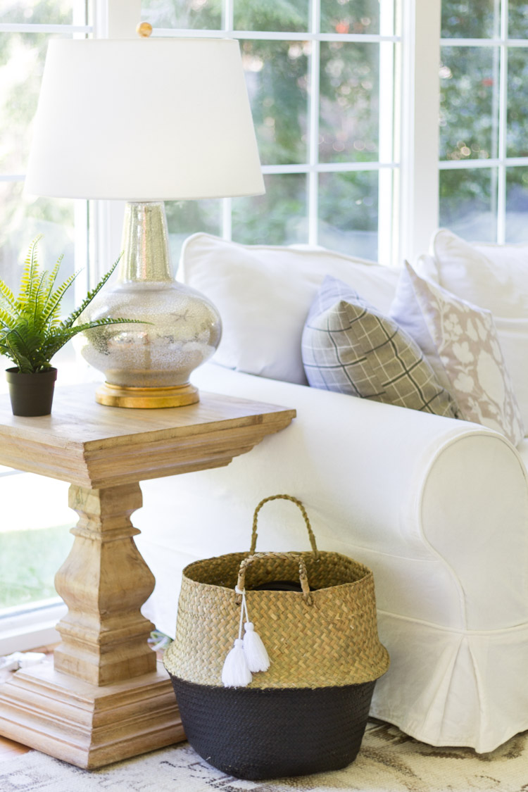 Black and straw basket beside white couch.
