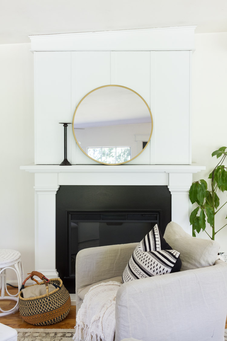 Fireplace mantel with large round mirror on it.