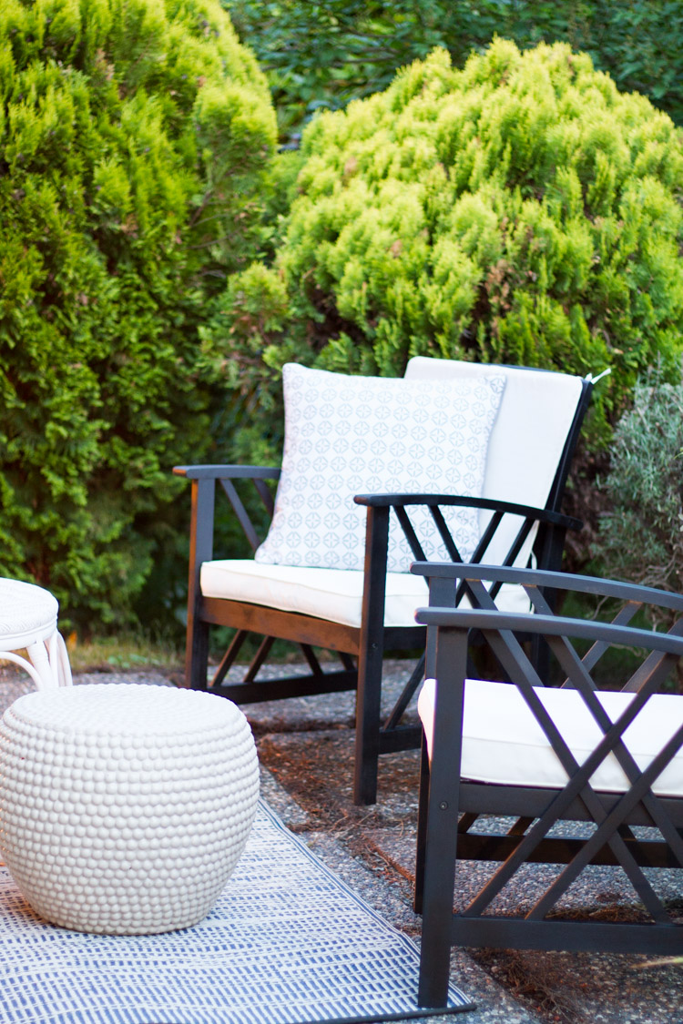 Wood patio chairs with white cushions.