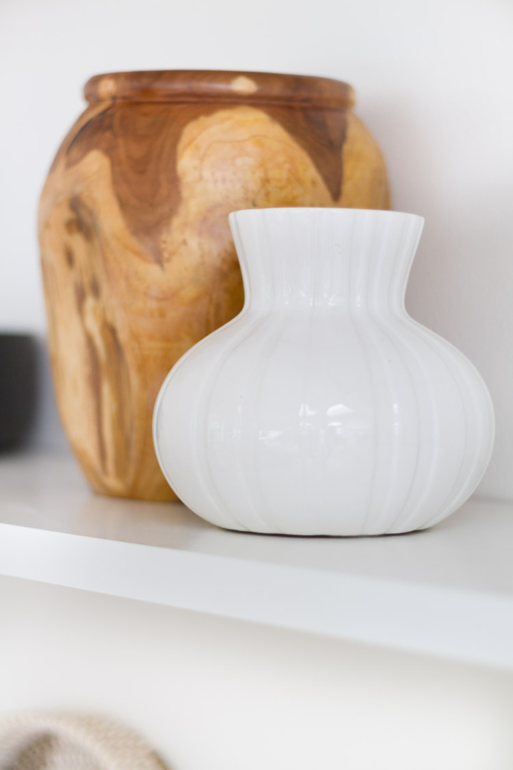 White and wooden vase on counter.