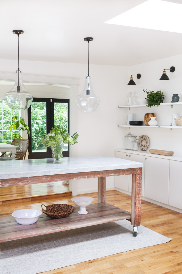 White kitchen, pendant lights, and kitchen island.