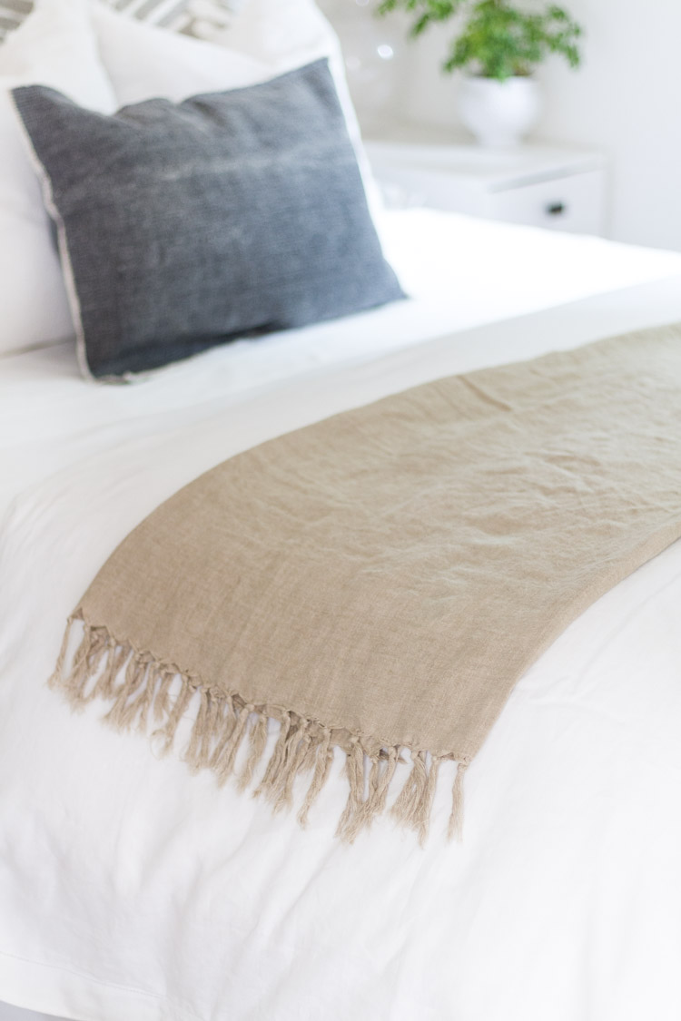 Linen throw blanket on bed.