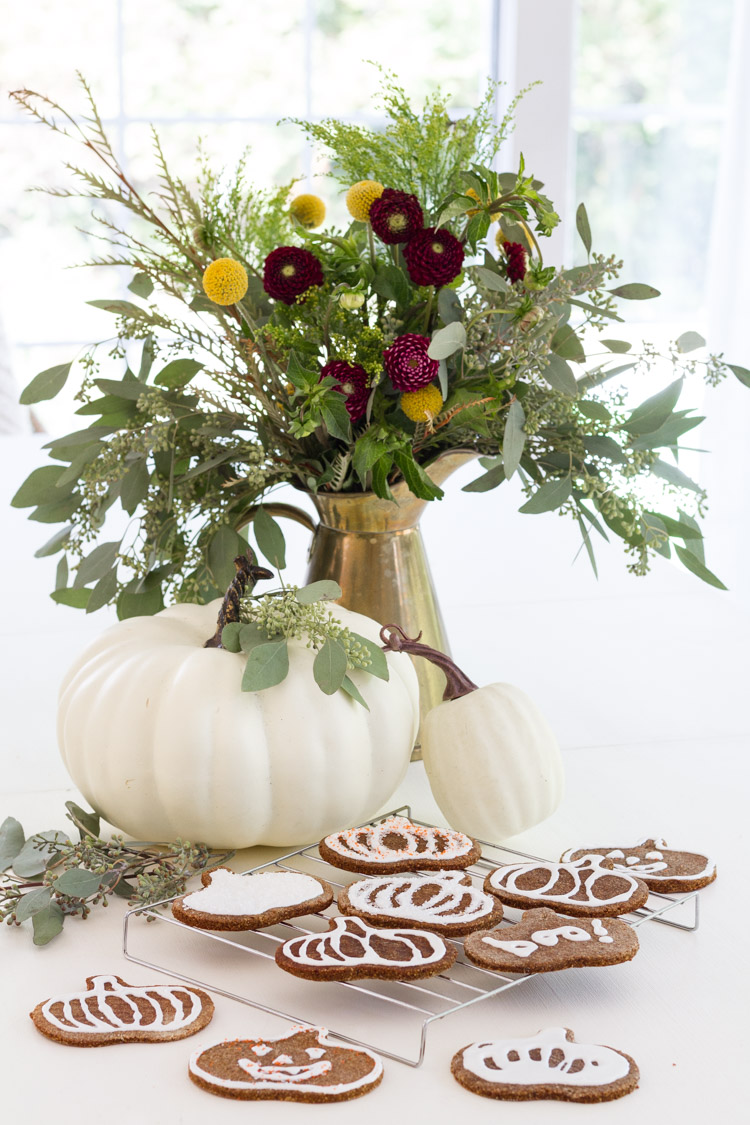 Iced cookies on the counter with a pumpkin and flowers in a vase.
