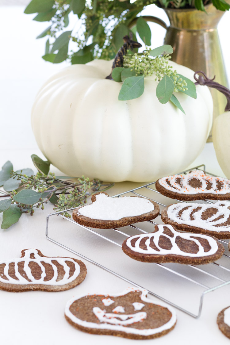 Large white pumpkin on counter with iced cookies around it.
