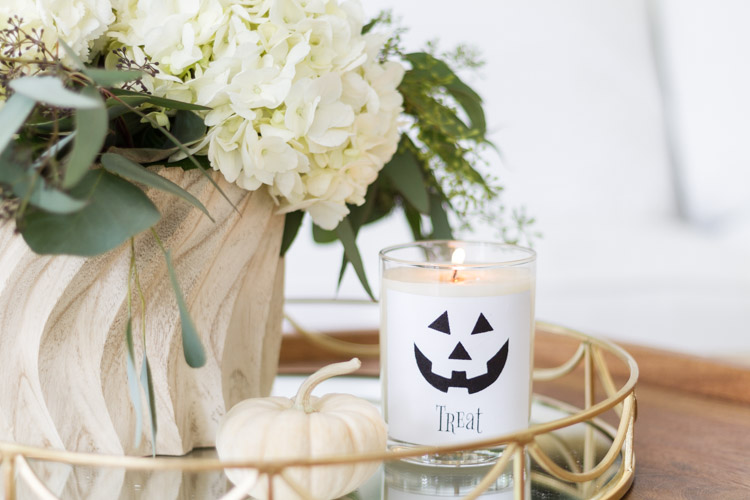Candle with the treat side showing beside white hydrangeas.