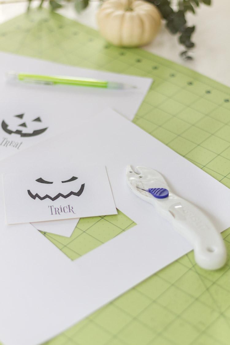 The stickers lying beside an pen on a cutting mat.