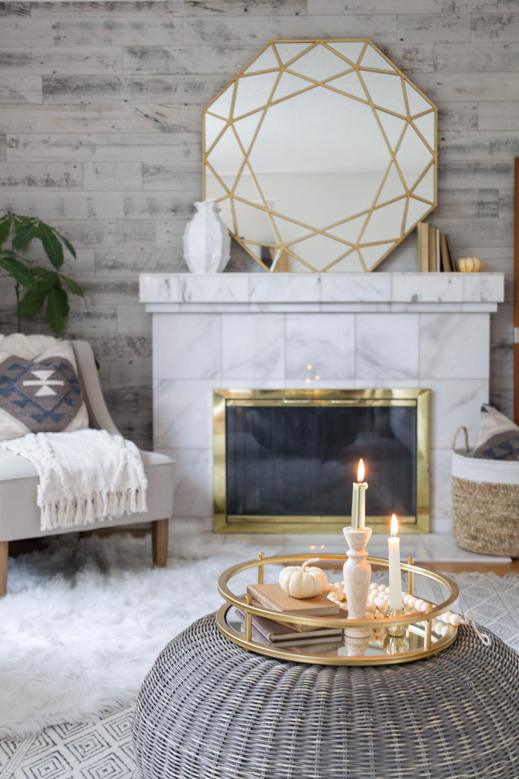 Large gold mirror above the fireplace, with faux fur in front of it and brass detailing.