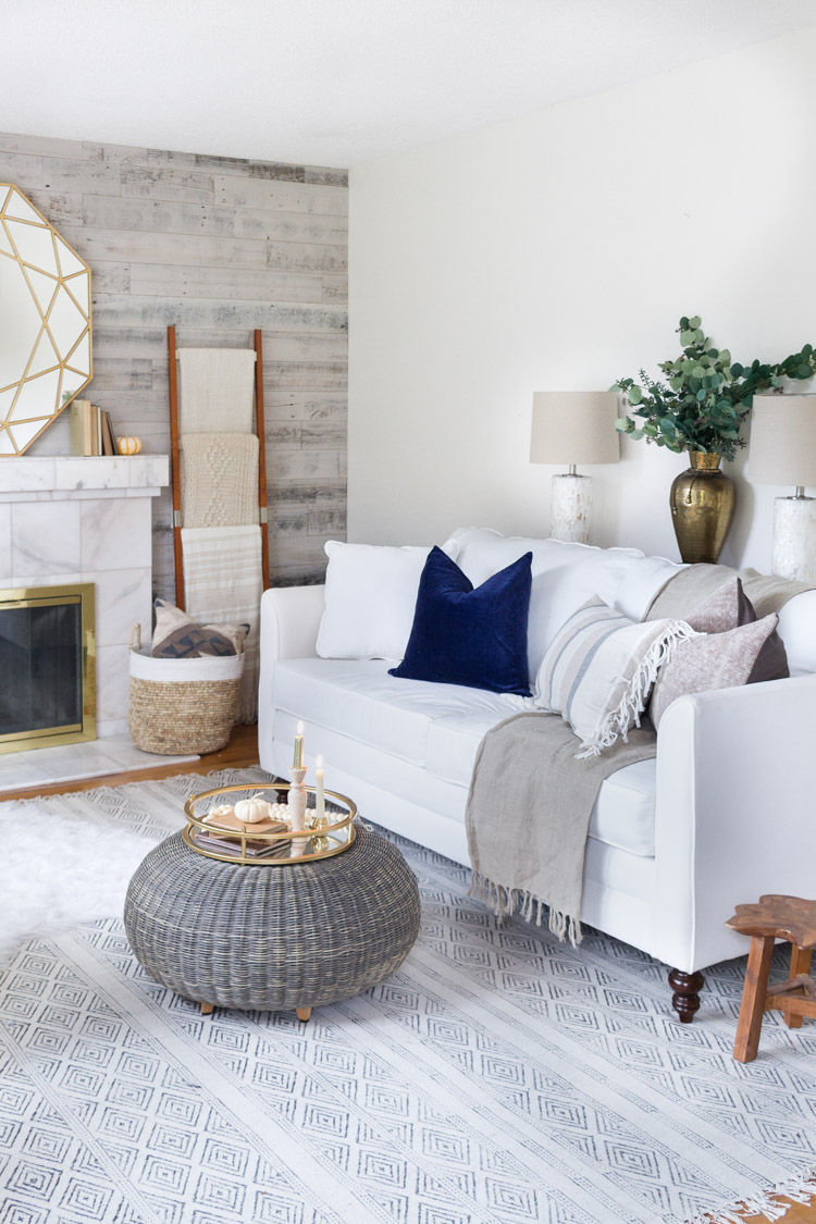 Neutral living room with white couch, a marble fireplace, and blue and white rug.