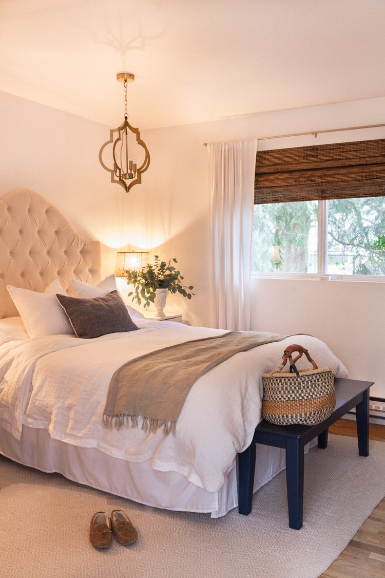 Large bed in bedroom with tufted headboard and a small bench in front of bed with basket on it.