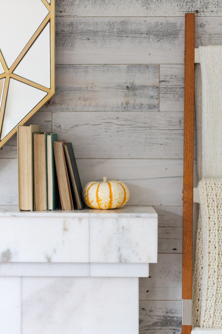 Marble fireplace mantel with books on it and a small pumpkin.