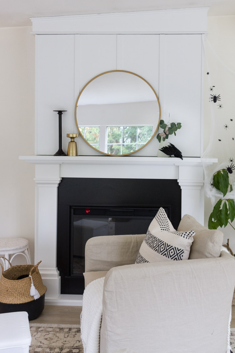 Large round gold mirror on the white fireplace mantel.