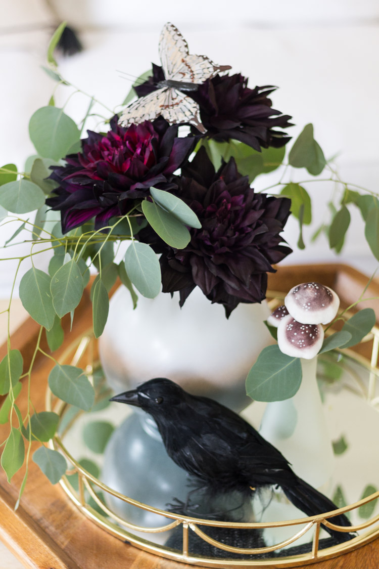 Black crow and dark purple flowers in coffee table.