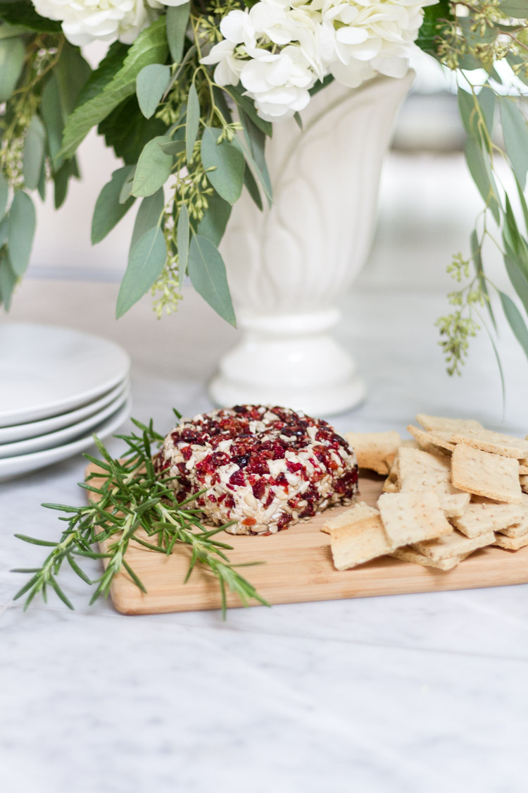Vegan Cranberry Cheese Loaf with Almond Crackers on a wooden cutting board.