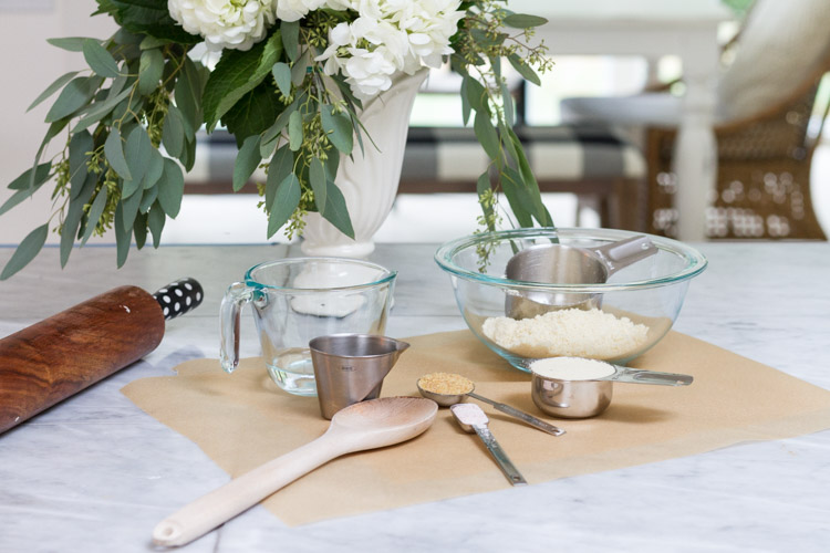 Clear mixing bowls, wooden spoon, measuring cups and a rolling pin on counter.
