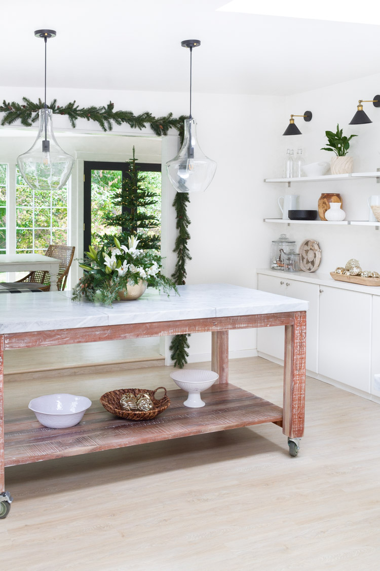 A white kitchen with evergreen around the window and floral touches on the island.