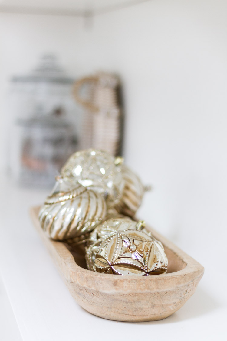 Very ornate Christmas ornaments in a wooden bowl on the shelf.