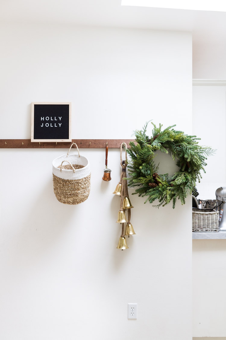 A green Christmas wreath, bells and a basket hanging on a coat rack in the kitchen.