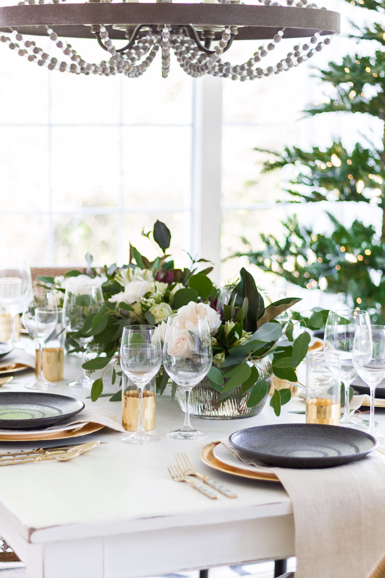 White wooden dining table, with eucalyptus leaves and roses as a centerpiece.