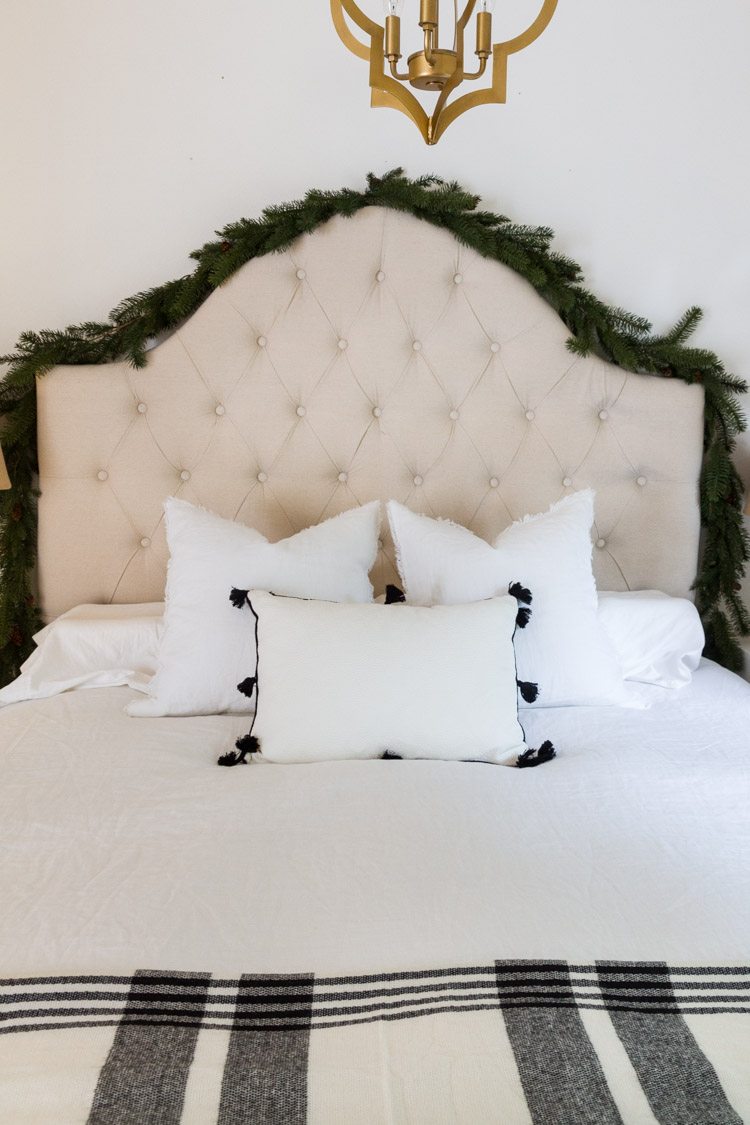 A white bed with 3 pillows on it, and evergreen around the headboard.