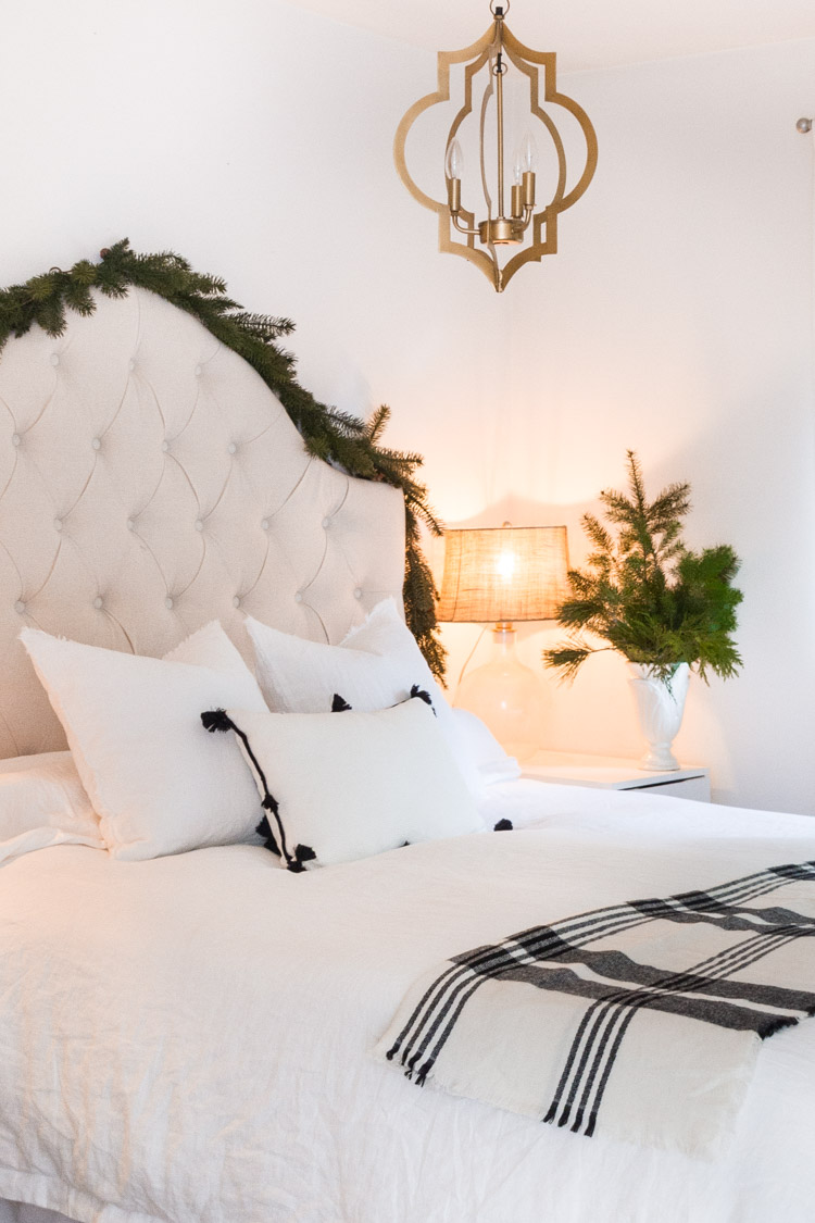 A white bed with white headboard and evergreen along the headboard.