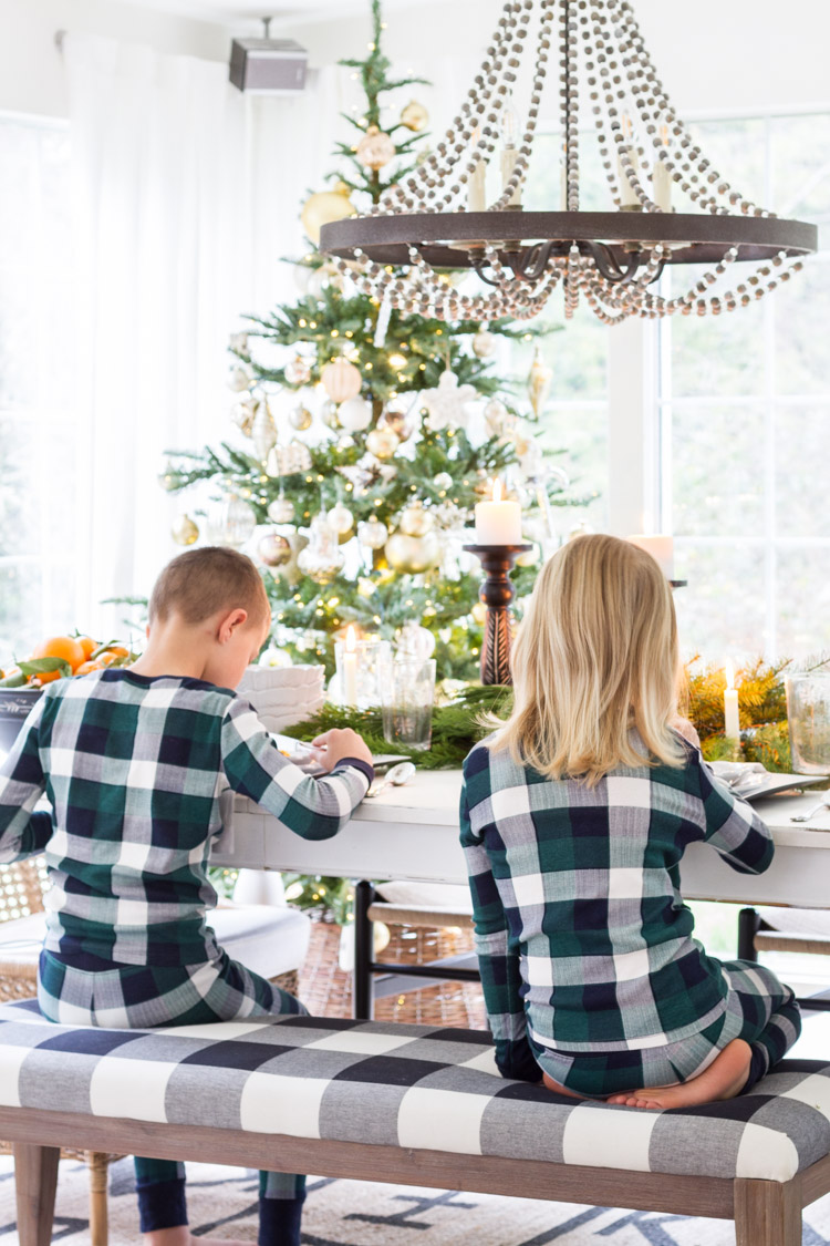 Two kids sitting on a dining room bench, in matching checkered green PJ's eating the waffles.