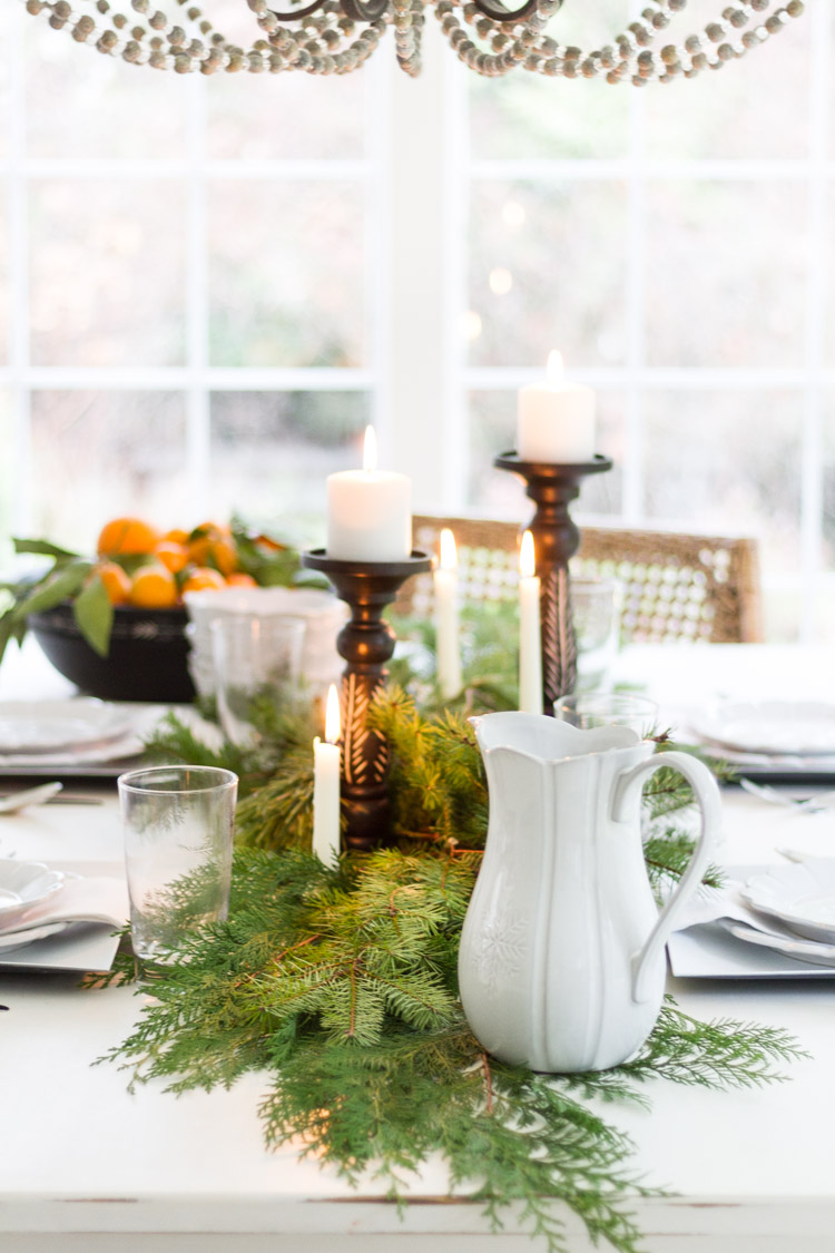 A white pitcher, a branch from a Christmas tree, candles all on the table.