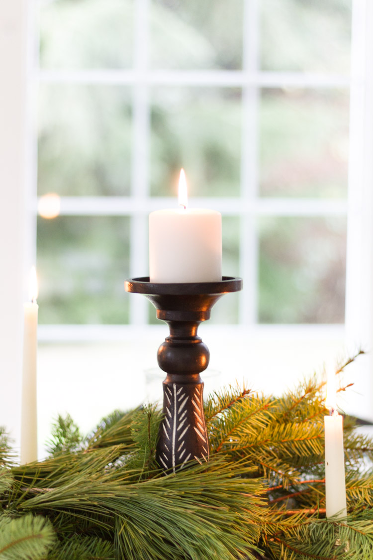 A single candle surrounded by branches of a pine tree on the table.