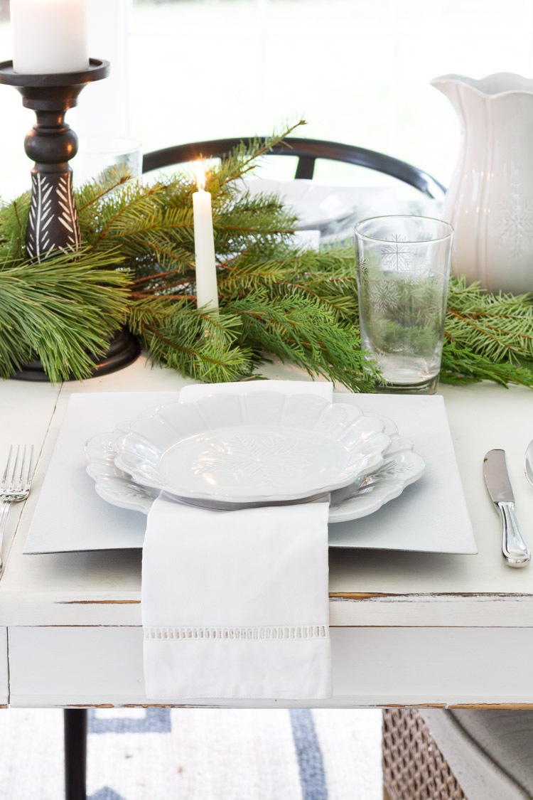 White plates on the table with a white napkin.