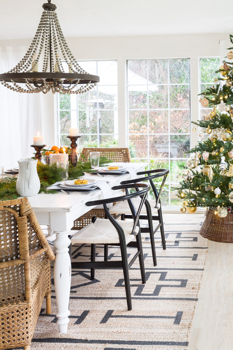 Black chairs, a wooden table, a beaded chandelier all decorated for Christmas brunch.