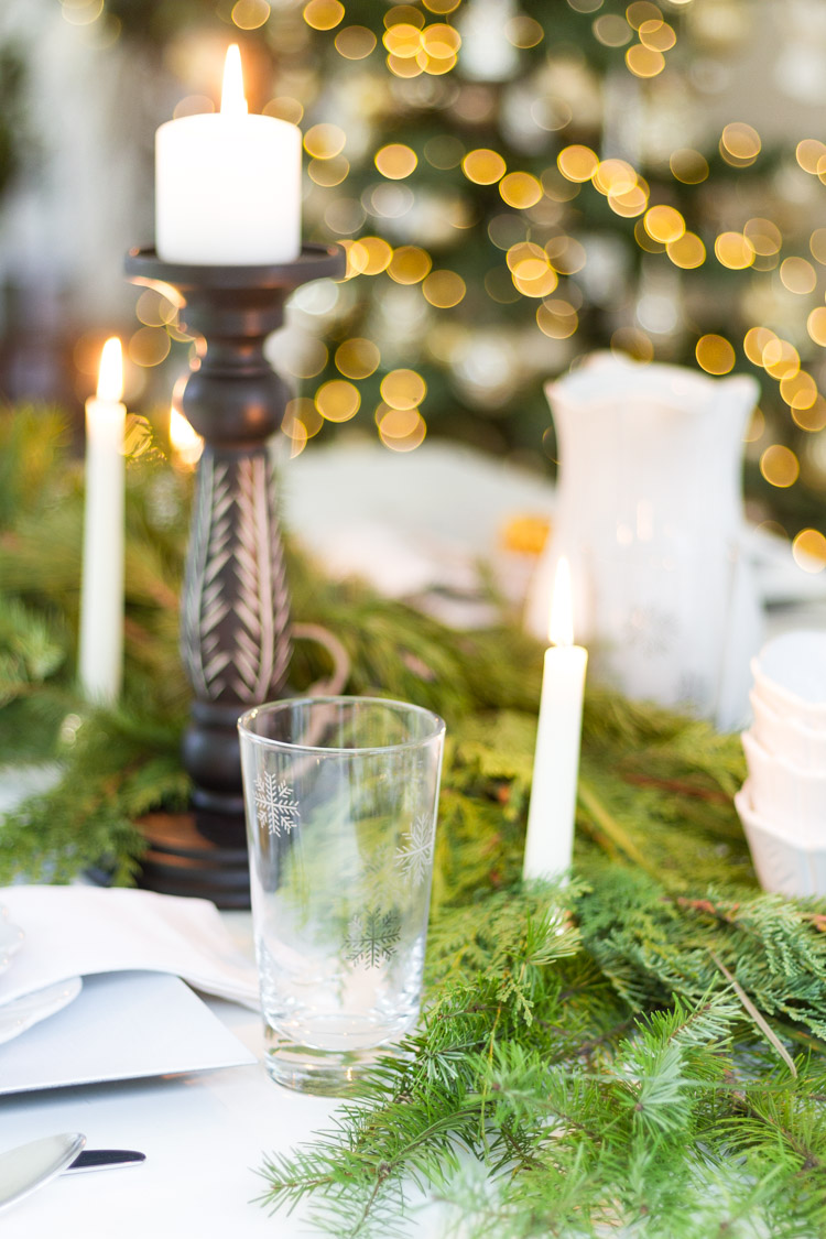 A clear glass with a snowflake etched on it, lit candles and pine branches on the table.