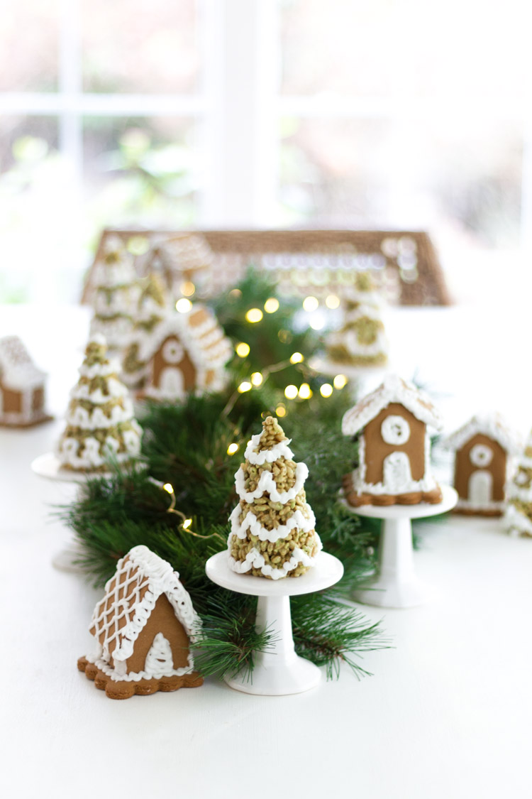 Little gingerbread houses and little Christmas trees on stands beside them on the table.